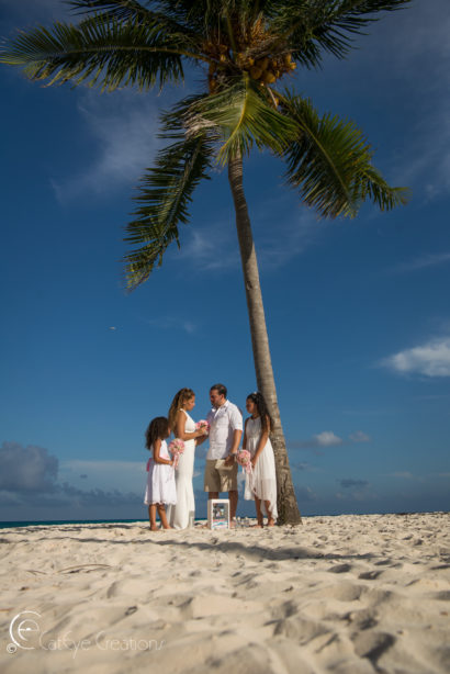 wedding photography intimate ceremony with couple and 2 children under a palm tree on the beach